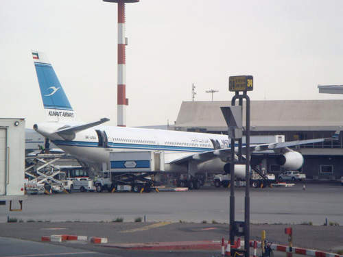 A Kuwait Airways A340-300 parked at a gate at Kuwait airport.