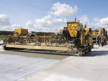 One of the GOMACO paving trains. The paving train, consists of a PS-2600 placer / spreader, four-track GHP-2800 with auto-float, and a T/C-600 texture / cure machine.