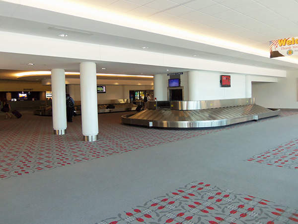 The baggage claim area inside the Quad City International Airport terminal has two rotating conveyors and public seating space. Image courtesy of Farragutful.