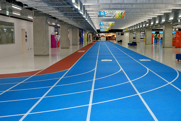 The interior of the new terminal mimics a running track with a system of red and blue running lanes. Image courtesy of Narita International Airport Corporation (NAA).