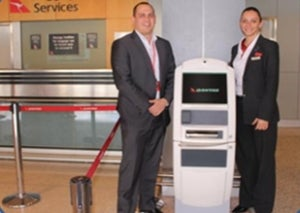 Quantas employees with the BagAssist kiosk